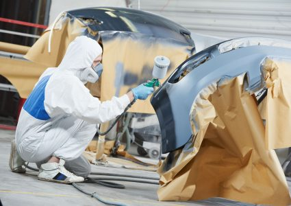 An image of an Auto Mechanic Worker spraying painting various car pieces.